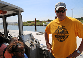 Dr. Aaron Spence stands in a boat surrounded by students.