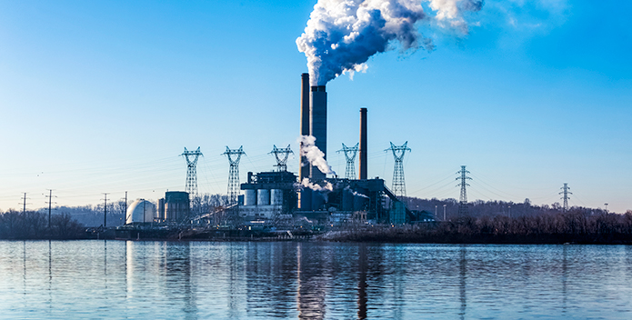 Photo of smoke billowing from a power plant smokestack, reflected in the river running alongside.