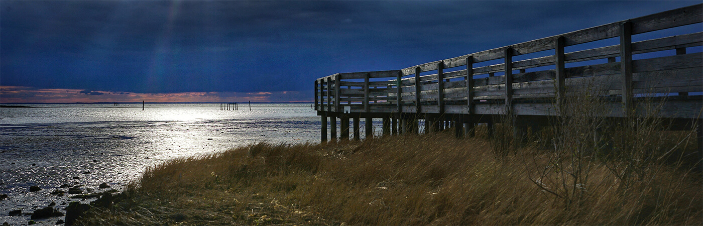 Photo of dock overlooking the Bay under stormy skies